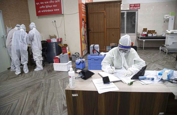 An Indian doctor wearing PPE kits writes thee details of a patient before collecting samples for swa