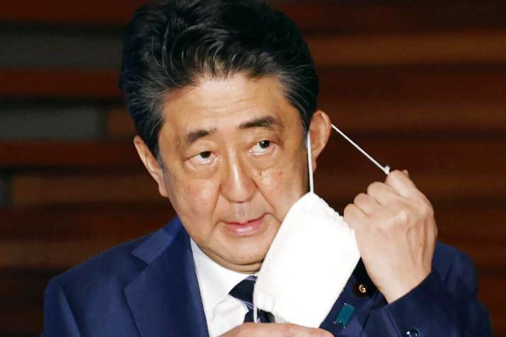 Japan's Prime Minister Shinzo Abe removes a face mask as he speaks at a press conference in Tokyo Th