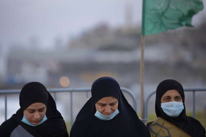 Muslim worshippers wearing protective face masks gather for Eid al-Fitr prayers marking the end of
