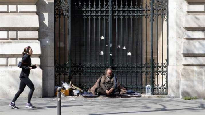 A woman runs as a homeless man looks on during the lockdown