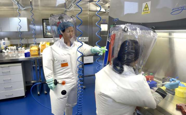 In this Thursday, Feb. 23, 2017 file photo, Shi Zhengli works with other researchers in a lab at the