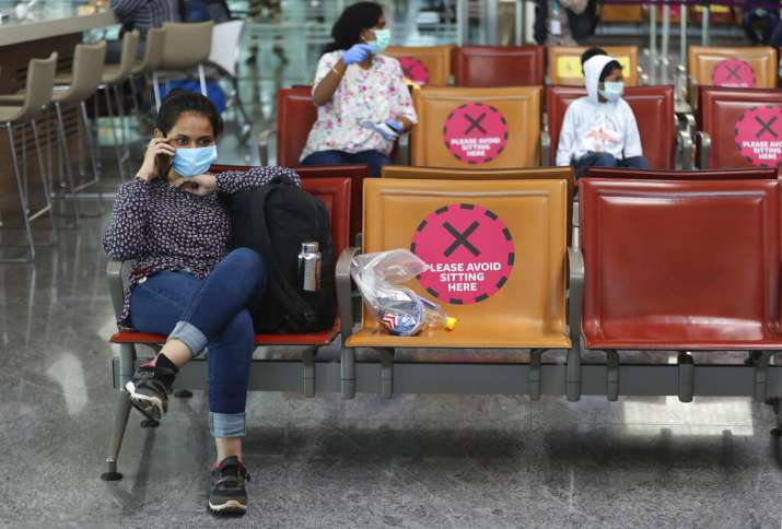 Passengers wearing face masks are seated maintaining social distancing before boarding their flight