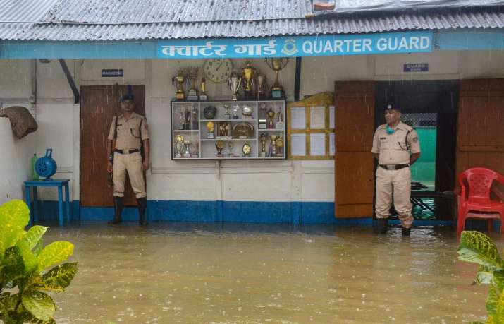 Dibrugarh: CRPF personnel stand guard submerged in floodwaters at CRPF (171) quarter following heavy