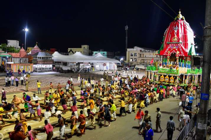 Priests and policemen pull the three chariots of Lord Jagannath, Balarama, and Subhadra from the con
