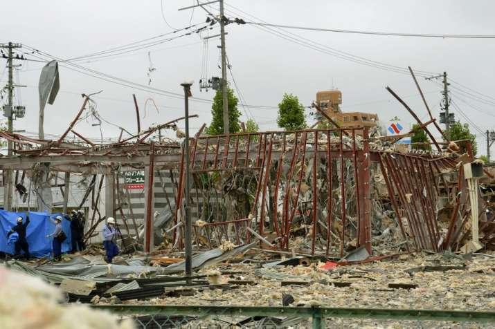 Investigators work near a damaged building following an explosion in Koriyama, Fukushima prefecture,