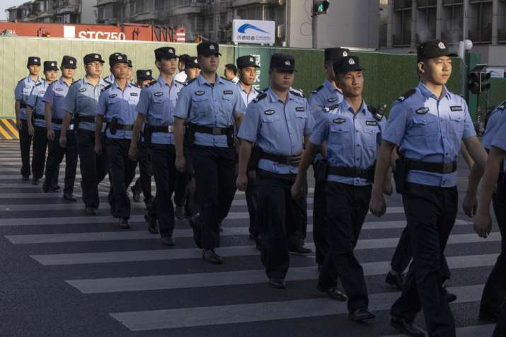 Chinese policemen prepare for duty around a neighborhood sealed off before the official closure of t