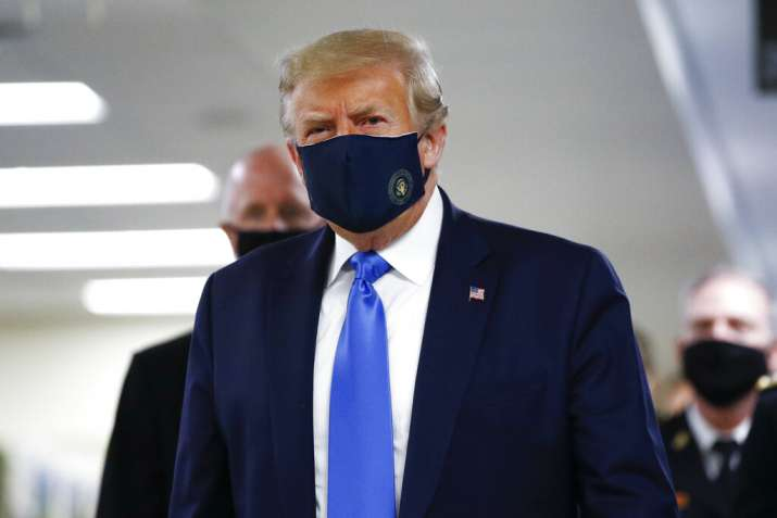 President Donald Trump wears a mask as he walks down the hallway during his visit to Walter Reed Nat