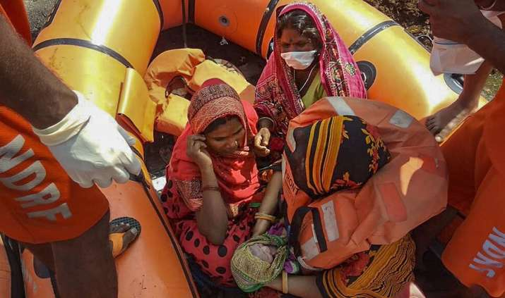 East Champaran: NDRF personnel hold a new-born baby on a