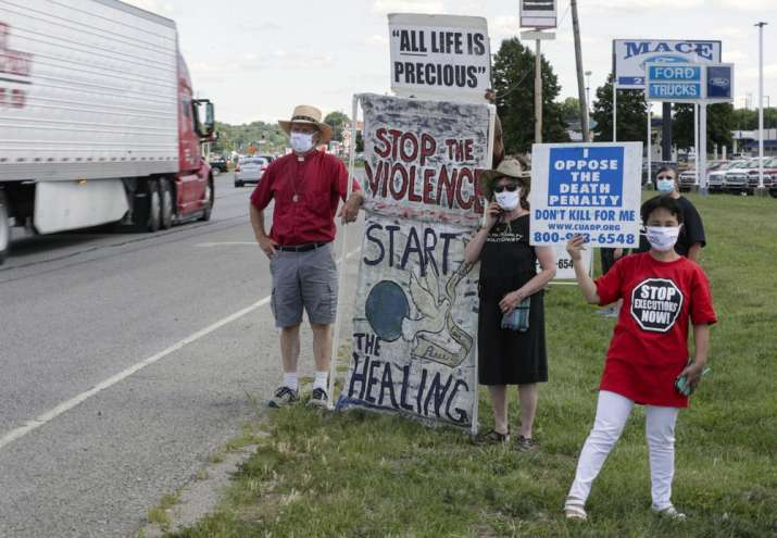 India Tv - Protesters against the death penalty gather in Terre Haute, Ind., Monday, July 13, 2020. Daniel Lewis Lee, a convicted killer, was scheduled to be executed at 4 p.m. in the federal prison in Terre Haute. He was convicted in Arkansas of the 1996 killings of gun dealer William Mueller, his wife, Nancy, and her 8-year-old daughter, Sarah Powell.
