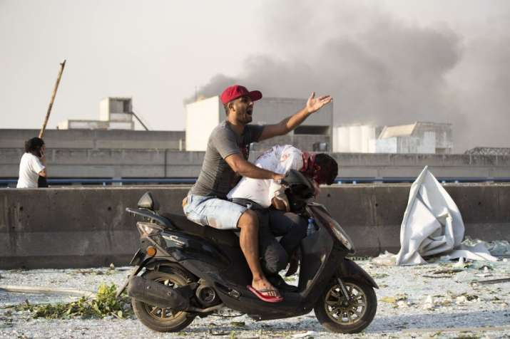 India Tv - A man evacuates an injured person after a massive explosion in Beirut, Lebanon, Tuesday, Aug. 4, 202