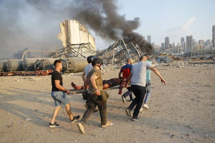 India Tv - Civilians carry a person at the explosion scene that hit the seaport, in Beirut Lebanon, Tuesday, Au