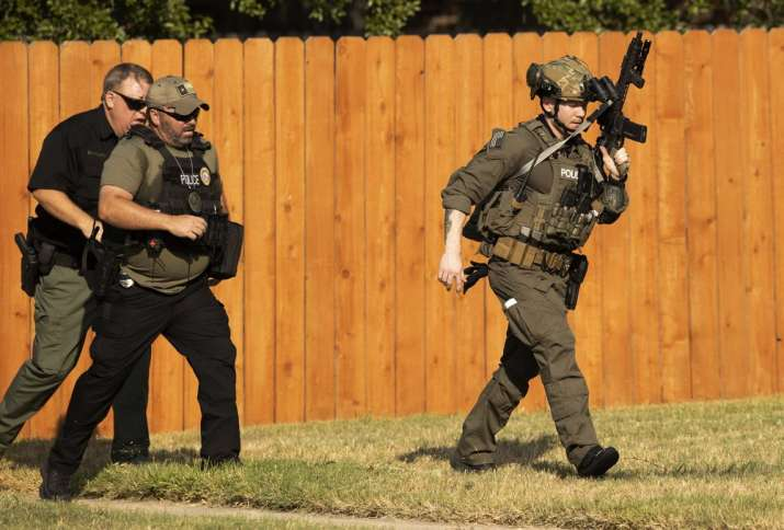 Police officers work near the house in Cedar Park, Texas, where a person remained barricaded Sunday,
