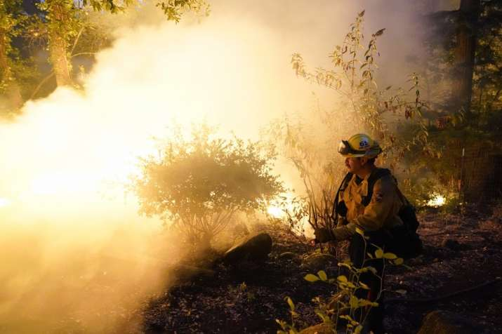 Firefighter Jeremy Damon of the Nevada Yuba Placer Fire Dept. monitors a controlled burn in the back