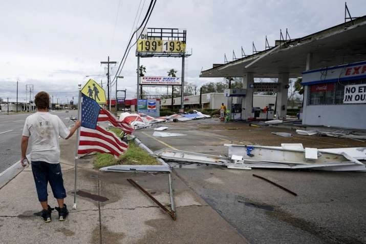 Dustin Amos walks near debris at a gas station on Thursday, Aug. 27, 2020, in Lake Charles, La., aft