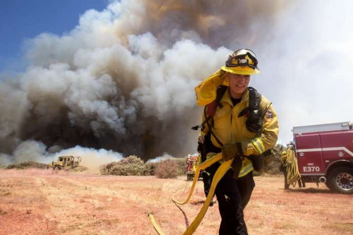 A firefighter battles a brush fire at the Apple Fire in Cherry Valley, Calif., Saturday, Aug. 1, 202