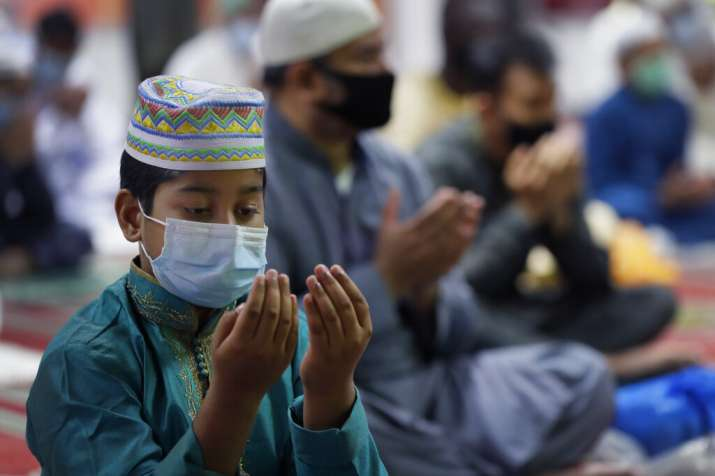 A young Muslim wears a face mask to protect against coronavirus as Muslims gather to pray at Minhaj-