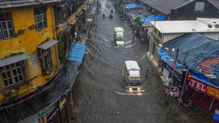 India Tv - Mumbai: Vehicles ply on a waterlogged street during heavy rains, at Byculla area in Mumbai, Wednesda