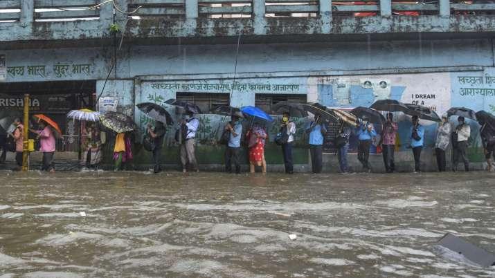 India Tv - Mumbai: Pedestrians cross a waterlogged street during heavy rains, at at Byculla area in Mumbai, Wed