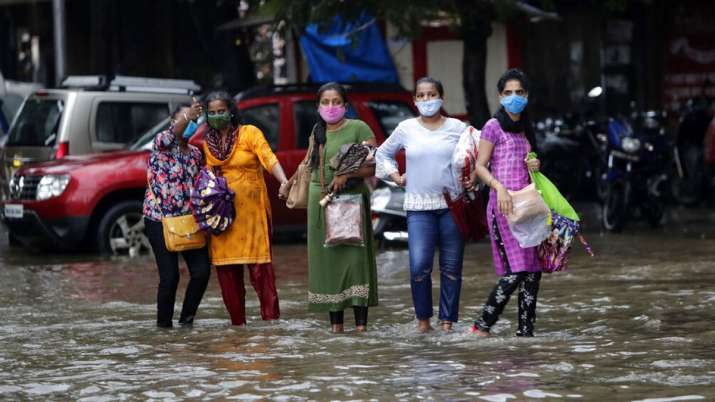 India Tv - People wade through a water logged street during heavy rain in Mumbai, India, Wednesday, Aug. 5, 202