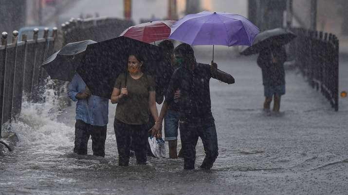 India Tv - Mumbai: Pedestrians cross a waterlogged street during heavy rains, at Sion in Mumbai