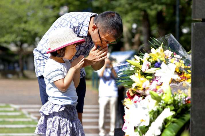 India Tv - A man and his daughter pray for the victims of U.S. atomic bombing at the Atomic Bomb Hypocenter Par