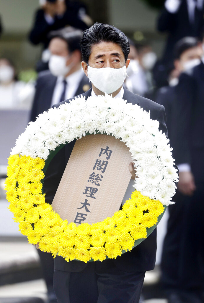 India Tv - Japanese Prime Minister Shinzo Abe carries the wreath to offer during a ceremony to mark the 75th an