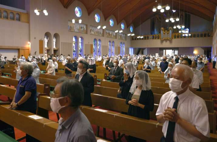 India Tv - Christians, wearing face masks, pray for the victims of U.S. atomic bombing during a mass at Urakami