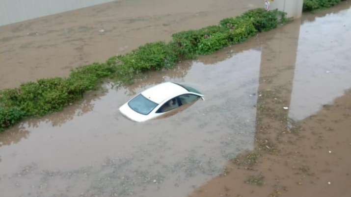 India Tv - A submerged car after heavy rain in Gurugram on Wednesday