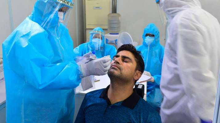 Health workers collect swab sample of a person at Indo-Israel Non-Invasive Raid Covid -19 test study