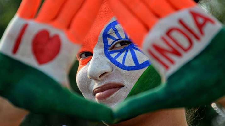 India Tv - A girl with her face and hands painted in tricolour poses for a photograph, on the eve of Independen