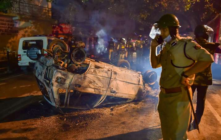 Bengaluru: Police stand next to the charred remains of a