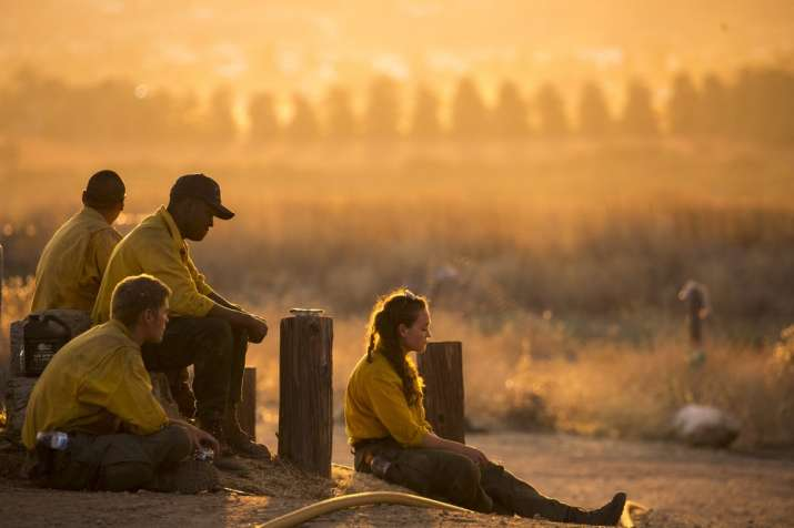Firefighters rest during a wildfire in Yucaipa, Calif., Saturday, Sept. 5, 2020. Firefighters trying