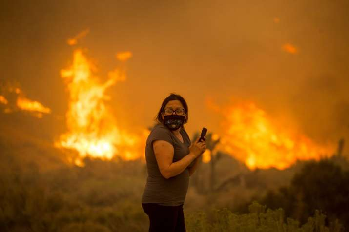 A woman watches as the Bobcat Fire burns in Juniper Hill, Calif., Friday, Sept. 18, 2020. (AP Photo/