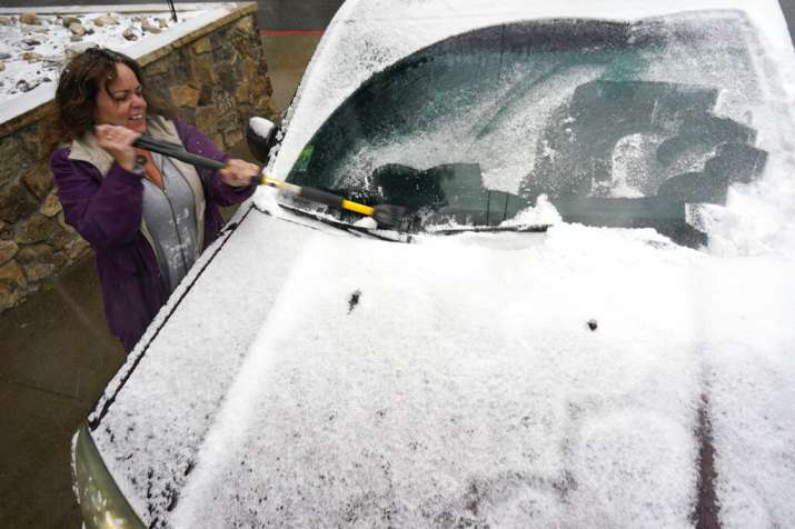 Diane Lee cleans the windshield of her sports-utility
