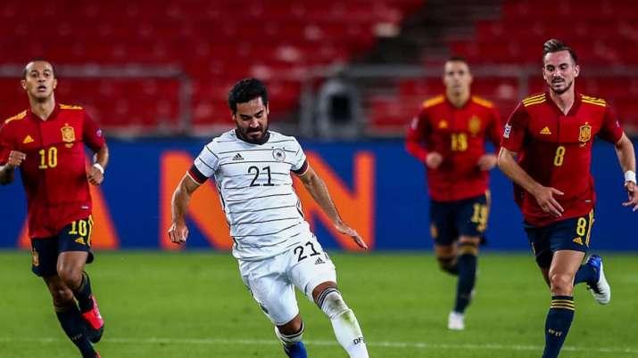 Germany's Ilkay Gundogan, center, runs with the ball past