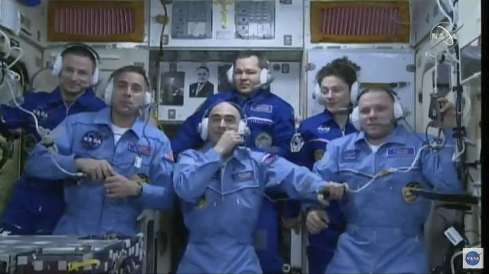 India Tv - In this image from video made available by NASA, newly-arrived International Space Station crew members, foreground from left, Chris Cassidy, Anatoly Ivanishin and Ivan Vagner, stand with outgoing crew members, background from left, Andrew Morgan, Oleg Skripochka, and Jessica Meir during a news conference on Thursday, April 9, 2020.