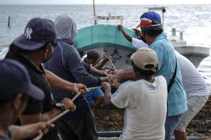 Fishermen pull in a boat before the arrival of Hurricane Delta in Puerto Juarez, Cancun, Mexico, Tue