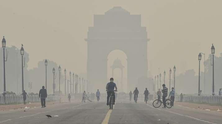 A cyclist rides near India Gate amid hazy weather