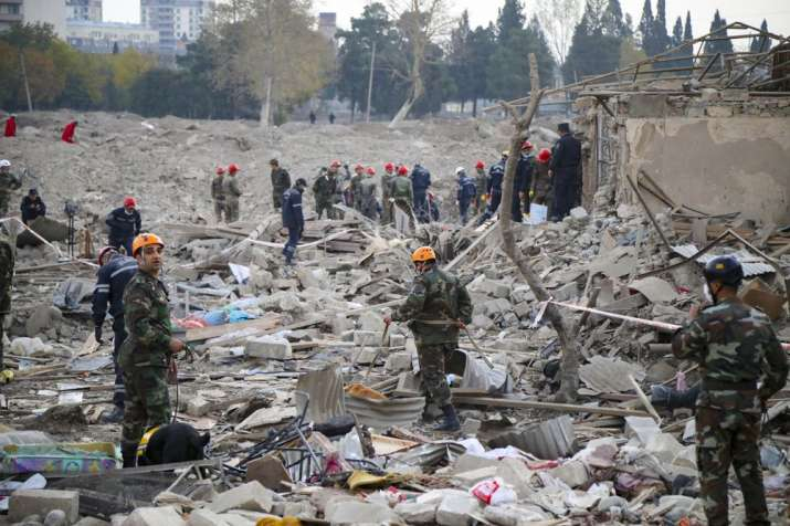 Soldiers and firefighters search for survivors in a residential area that was hit by rocket fire ove