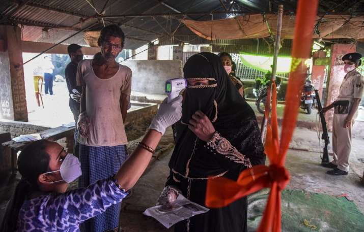 India Tv - Patna: A voter undergoes thermal screening at a polling station before casting her vote for the firs