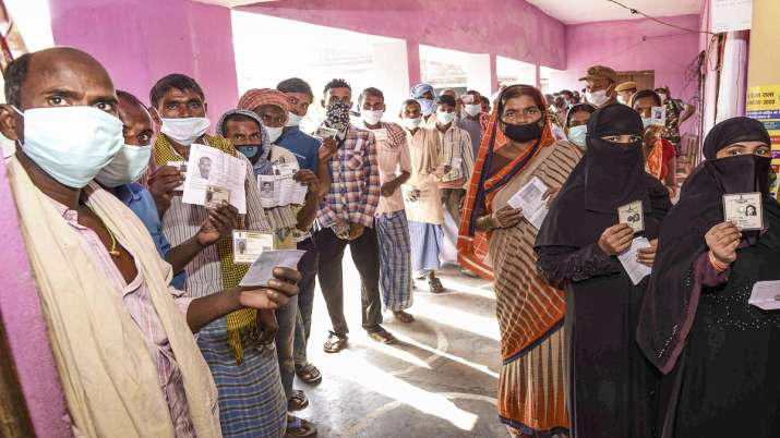 Voters show their identity cards as they stand in queues