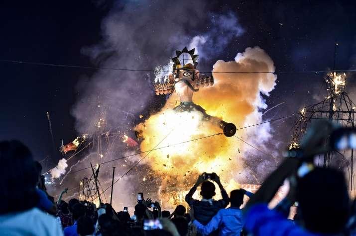 People look on as an effigy of demon king Ravana burns