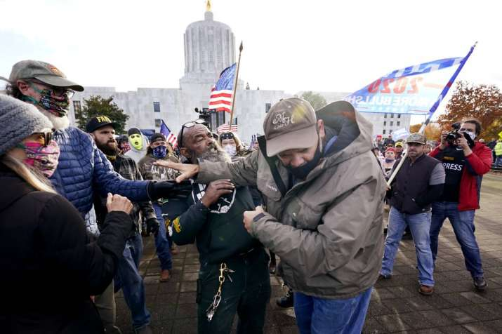 India Tv - Supporters of President Trump, left, fight with a counterprotester, center right, at the Oregon State Capitol building Saturday, Nov 7, 2020, in Salem, Ore. Democrat Joe Biden defeated Trump to become the 46th president of the United States on Saturday.