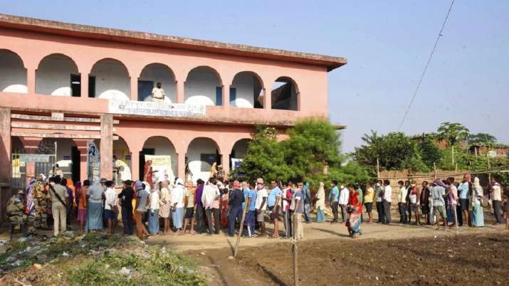 Voters stand in a queue to cast their votes outside a