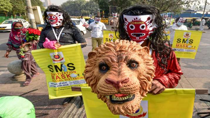 Volunteers, wearing masks, participate in a COVID-19 awareness campaign as coronavirus cases rise ac