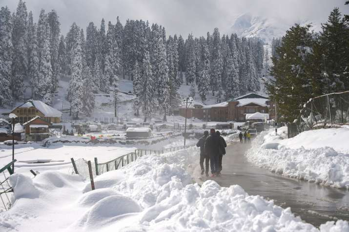 Gulmarg: People walk on a road after the seasons first