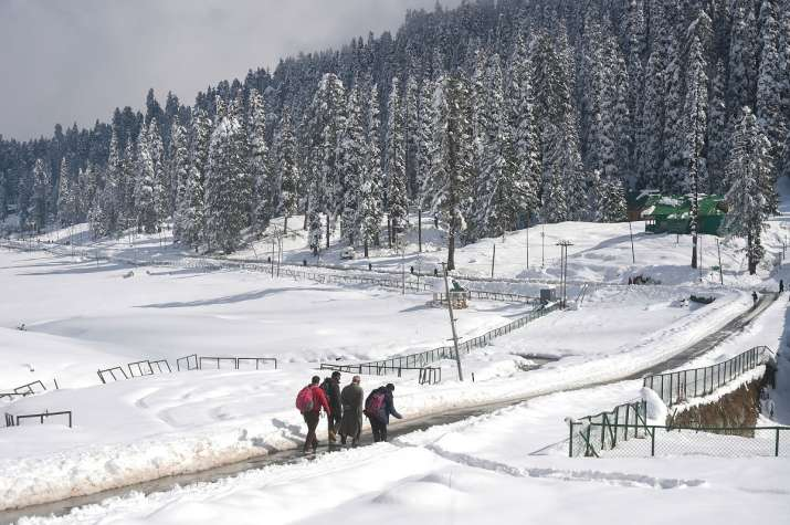 India Tv - Gulmarg: People walk down a road after the seasons first snowfall, at Gulmarg in Baramulla district of north Kashmir, Monday, Nov. 16, 2020. Authorities have issued an avalanche warning in four districts of the Valley as the higher reaches of the Union Territory received moderate to heavy snowfall, while the plains were lashed by rains.