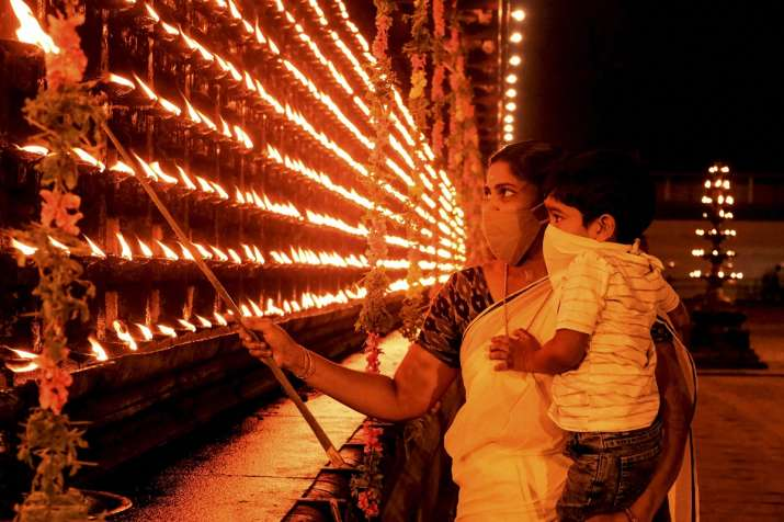 People light earthen lamp (Diyas) on the occasion of Diwali, in Thrippunithura