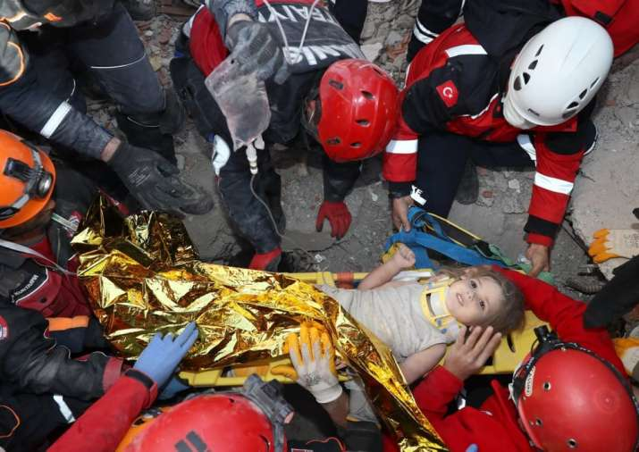 Rescue workers, who were trying to reach survivors in the rubble of a collapsed building, surround A