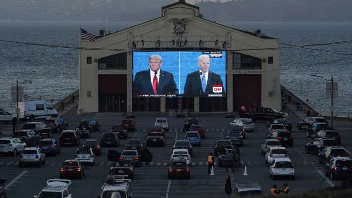 People watch from their vehicles as Donald Trump and Joe